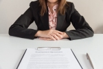 55276389 - businesswoman sitting with employment agreement in front of her.